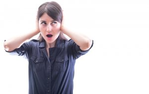 woman-covering-her-ears-while-wearing-blue-shirt